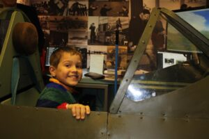 A young visitor flies the spitfire simulator at Maidenhead Heritage Centre